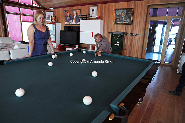 Ibrahim Ibrahimov, an Azerbaijani oligarch and billionaire, plays billards as his wife, Valida Ibrahimli, looks on in one of several houses on his Caspian seaside property he used to inhabit with his family in the Garadagh region just southwest of Baku, Azerbaijan on July 18, 2012.  Ibrahimov is the developer behind the Khazar Islands artificial islands project; in his private life, he enjoys building a home for his family, moving in, and then quickly tires of the property before building a new home on an adjacent lot on his seaside lands.