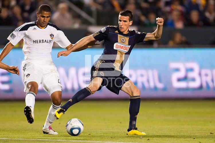Philadelphia Union forward Sebastien Le Toux (9) attempts to move through LA Galaxy defender Leonardo (22). The LA Galaxy defeated the Philadelphia Union 1-0 at Home Depot Center stadium in Carson, California on  April  2, 2011....