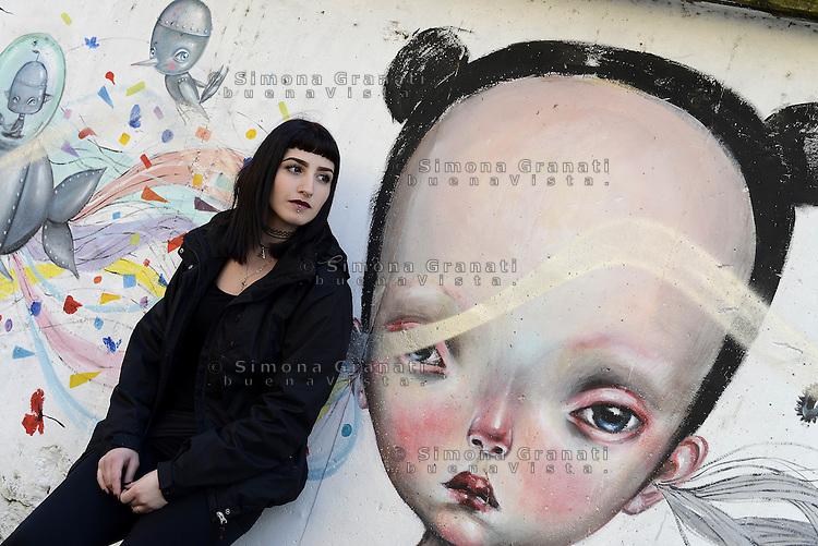 Roma, marzo 2015<br /> Murales nel quartiere popolare del Quadraro nella periferia sud est di Roma.<br /> Una ragazza posa davanti il murales di Dilka Bear.