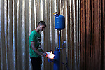 Palestinian student Ibrahim Saad, 18, tests his project at his home's workshop, in Gaza City on Sept. 26, 2013. The project aims to produce hydrogen gas by analysing water with chemicals, which uses to run an electricity generator and as cooking gas. Gaza Strip faces a fuel crisis since the Egyptian army launched a crackdown on the border tunnels linking the Gaza Strip to Egypt's Sinai Peninsula, which are dedicated largely to transporting items restricted by Israel, including fuel, the coastal enclave home to roughly 1.7 million people has been hit by a crippling energy crisis that has affected public transport, electricity and construction. Photo by Ashraf Amra