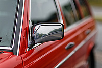 The wing mirror of the Mercedes W123 series 230TE estate version, outside the Penderyn Whisky Distillery in south Wales, UK. Tuesday 19 June 2018