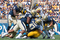the Pitt defense gang tackles an Iowa ball carrier. Shown are Todd Thomas (8), Khaynin Mosley-Smith (95), Matt Galambos (47) and Ray Vinopal (9). Iowa Hawkeyes defeated the Pitt Panthers 24-20 at Heinz Field, Pittsburgh Pennsylvania on September 20, 2014.