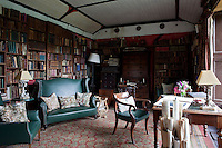 Old family photograph albums and estate maps are stored in the library which has walls lined with leather-bound books