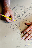 Artisan wood carver and furniture restorer, Luigi Mecocci, drafting antique furniture designs, in his workshop (bottega) on Via dei Velluti, Florence, Italy