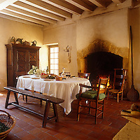 The large dining table is covered with a white cloth and laid for dinner