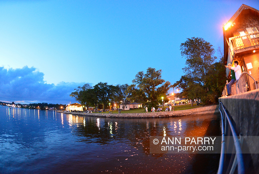 Port Washington, New York, USA. 26th June 2015. Along the shore of Manhasset Bay, at right, a woman points toward bay while sitting outside the John Kaelin Pavilion of the Town Dock Administration Building. Near center vista is waterside Sunset Park with brightly lit John Philips Sousa Memorial Band Shell during a concert, in the North Shore village on Long Island Gold Coast.