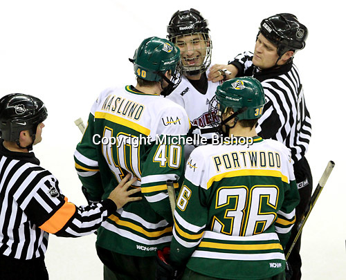 Linesman Nathan Stanton separates Nebraska-Omaha's Brent Gwidt  from Alaska-Anchorage's Daniel Naslund and Jade Portwood at the end of Saturday's game. (Photo by Michelle Bishop) ..