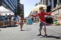 "Children hula hoop while New Yorkers ""dumpster dive"" in swimming pools made out of dumpsters on Park Avenue near Grand Central Station on 07 August 2010.  People were allowed 20-minute turns swimming in any of the three ""dumpster pools."""