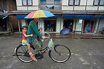 A woman peddles a bicycle in Tuingo, an ethnic Chin village in Myanmar.