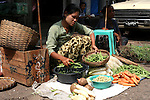 Woman selling vegetables on the street Theingyi Zei market in yangon