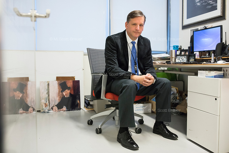 """Anthony Amore is the Directory of Security and Chief Investigator at the Isabella Stewart Gardner Museum in Boston, Mass., USA, seen here in his office on Tues., Dec. 5, 2017. Part of Amore's ongoing work is the investigation into the 1990 theft of 13 pieces from the museum: 10 paintings, 2 objects, and 1 etching. Among the paintings stolen were works by Rembrandt, Vermeer, Degas, and Manet. At left, on the ground, is a reproduction of Manet's """"Chez Tortoni."""" At right, hanging on the wall, is a reproduction of Vermeer's """"The Concert."""" Both works of art were stolen in the heist."""