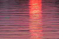Ripples create an impressionistic reflection of sunset's path of light across the surface of a river.