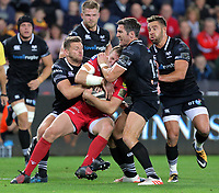 Hadleigh Parkes of the Scarlets (C) is held by Dan Biggar (L) and James Hook of the Ospreys (R) during the Guinness PRO14 Round 6 match between Ospreys and Scarlets at The Liberty Stadium , Swansea, Wales, UK. Saturday 07 October 2017