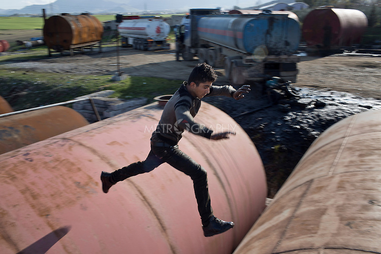 05/02/15 --TANJERO, IRAQ: Jamal (17) jumps between large storage drums at the refinery.<br /> <br /> Jamal, a Yezidi boy from Sinjar, lives with his displaced family next to an oil refinery in the Kurdish Region of Iraq. He and his cousins run the refinery 24 hours a day with little to no safety equipment. Reporting for this article was supported by a grant from the Pulitzer Center on Crisis Reporting