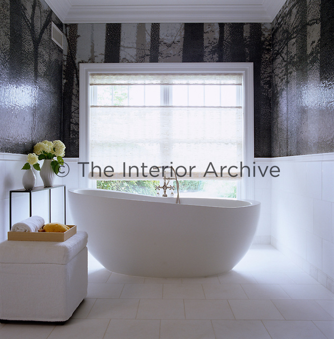 A contemporary shaped free-standing bath on a mosaic tiled floor in this black and white bathroom