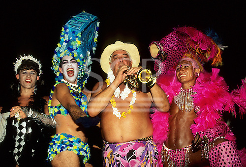 Rio de Janeiro, Brazil. Transvestites dressed in outlandish brightly coloured costumes, one playing a trumpet; Carnival.