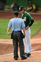 Clinton LumberKings manager Scott Steinmann (22) argues a call with umpire Ryan Doherty during a game against the Beloit Snappers on August 17, 2014 at Ashford University Field in Clinton, Iowa.  Clinton defeated Beloit 4-3.  (Mike Janes/Four Seam Images)