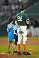 A pair of youth baseball players stand behind the pitchers mound with Greensboro Grasshoppers starting pitcher Trevor Rogers (26) during the National Anthem prior to the game against the West Virginia Power at First National Bank Field on June 1, 2018 in Greensboro, North Carolina. The Grasshoppers defeated the Power 10-3. (Brian Westerholt/Four Seam Images)