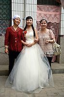 Bride Ren Jing poses for pictures with friends and family before her wedding to Da Fen in Pingliang, Gansu, China.  The newlyweds are members of the Hui ethnic minority, a Muslim ethnic group in China.