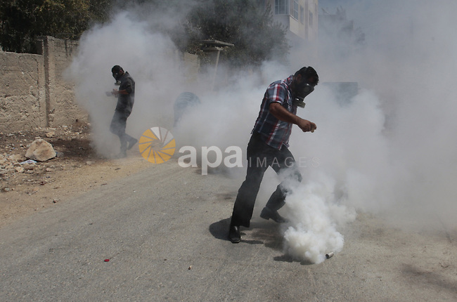 A Palestinian protester kicks back a tear gas canister fired by Israeli security forces during clashes following a protest against the expropriation of Palestinian land by Israel in the village of Kfar Qaddum, near Nablus in the occupied West Bank on August 23, 2013. Photo by Nedal Eshtayah