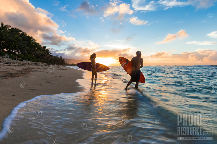 A surfer couple start to paddle out to catch some last waves before the sun sets, Waialua, North Shore, O'ahu.