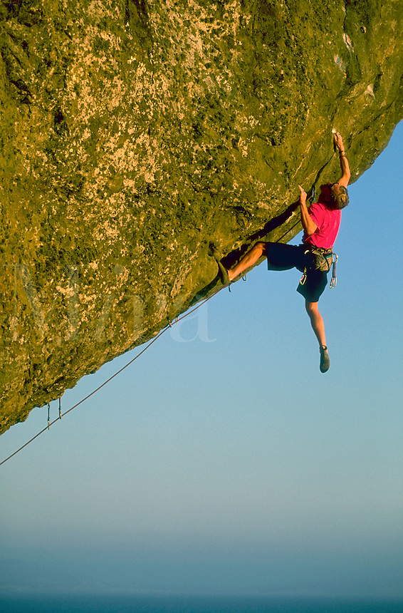 A rock climber hangs perilously by two hands from Endless Bumper in Marin County, California with blue sky in the distance.