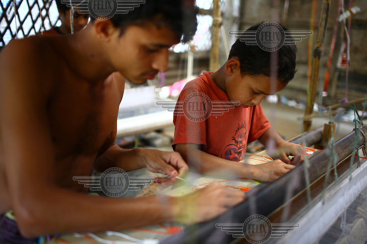 A boy weaves Jamdani cloth using a hand loom in a sari factory in Demra, Dhaka. She is one of several children working in this factory who work a 12-hour day but are unpaid as they are considered to be training. During the two years the training lasts the only payment they receive is three meals a day.