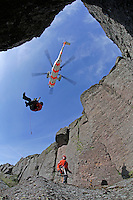 Practicing rescue from a ledge on a rock face using a rescue hoist.   Crew from Norwegian Air Force 330 squadron, flying Westland Sea King helicopter. The core mission of the squadron is SAR (search and rescue), but they also fly HEMS (Helicopter Emergency Medical Service), complementing the civilian air ambulance service.<br />