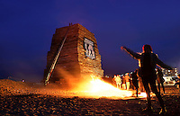 Nederland Den Haag.  2015 12 30.  De jaarlijkse opbouw van twee vreugdevuren bij Scheveningen en Duindorp. Vorig jaar werd het wereldrecord verbroken en werd het vreugdevuur van Duindorp  opgenomen in het Guinness Book of Records. Toeschouwers warmen zich op bij een vuurtje