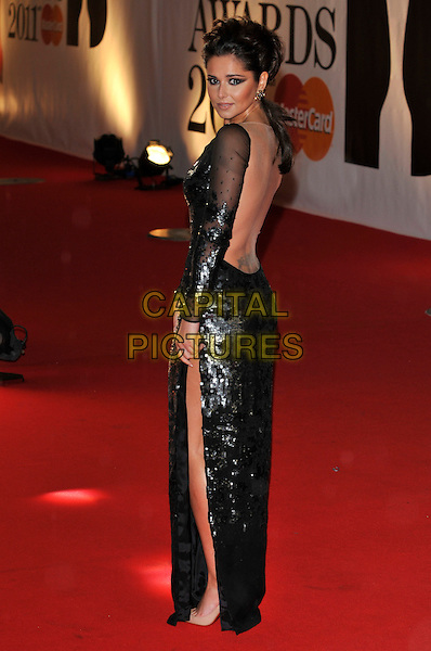 CHERYL COLE.The BRIT Awards 2011 at the O2 Arena, London, England..February 15th, 2011 .brits full length black dress sheer sequins sequined slit split looking over shoulder tattoo.CAP/PL.©Phil Loftus/Capital Pictures.