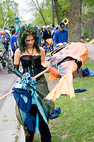 Puppeteer holding fish puppet representing beings who live in water. MayDay Parade and Festival. Minneapolis Minnesota USA