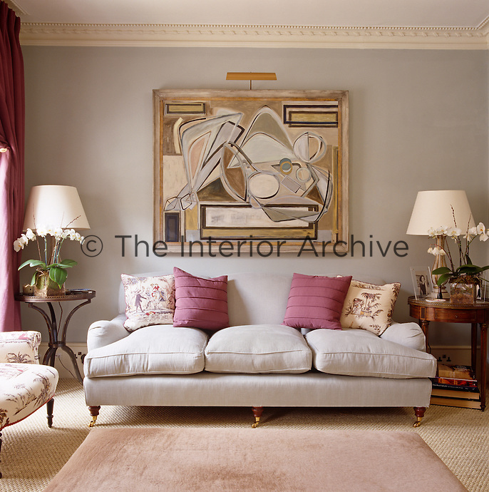 An abstract painting by Bianca Smith hangs on the wall above the pale grey sofa in the drawing room