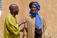 MALI, two men talking and laughing in village, they wear a Boubou, caftan made from Damask fabric and the Tagelmust, kind of turban and veil / MALI, Zwei Maenner unterhalten sich und lachen dabei