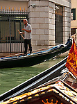A gondolier texting in Venice, Italy