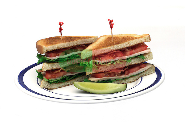 sandwich plate with triple decker turkey club, lettuce tomatoes, bacon, white bread, pickle on shadowless white background