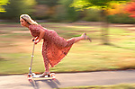 young woman in pretty summer dress riding scooter