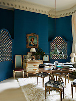 In the dining room, the painted chest, metal Chinoiserie lamp and deep blue walls create a sense of playful drama. Around the table, four dining stools are upholstered in fabric painted to look like a portrait by Picasso when pushed together.