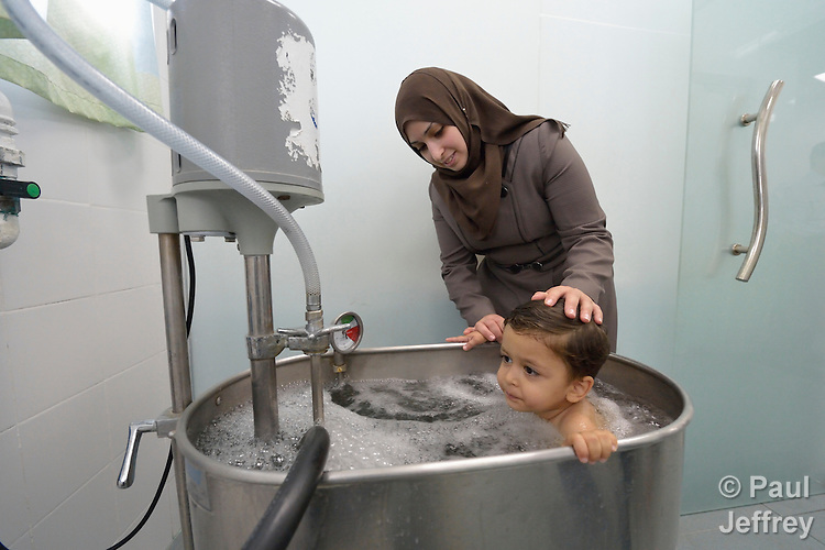 Three-year old Anas, who suffered a severe burn to her chest, is comforted by her mother Ola Yasin as the girl sits in a therapeutic bath in the Al Ahli Arab Hospital in Gaza City. The Anglican Church-affiliated hospital is a member of the ACT Alliance.<br /> <br /> The 2014 war provoked serious damage to Gaza's health infrastructure. Seventeen hospitals, 56 primary health care facilities and 45 ambulances were damaged or destroyed. Sixteen health care workers were killed and 83, most of them ambulance drivers and volunteers, were injured.