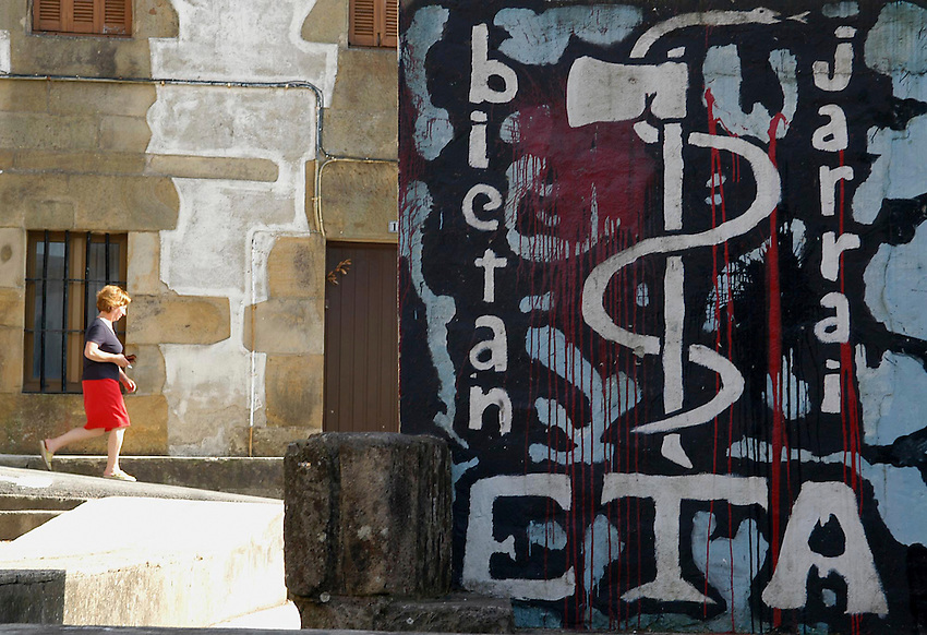 An unidentified woman walks past near a graffiti showing the symbol of ETA, a snake wrapped around an axe and words reading 'carry on' in Usurbil, Basque Country, Thursday May 26, 2005. Photo:Ander Gillenea