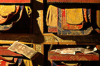 The upper chapel of the Yumbulagang fortress has a wall of Buddhist scriptures (sutra). Tourists and pilgrims often leave a small token of Chinese money..