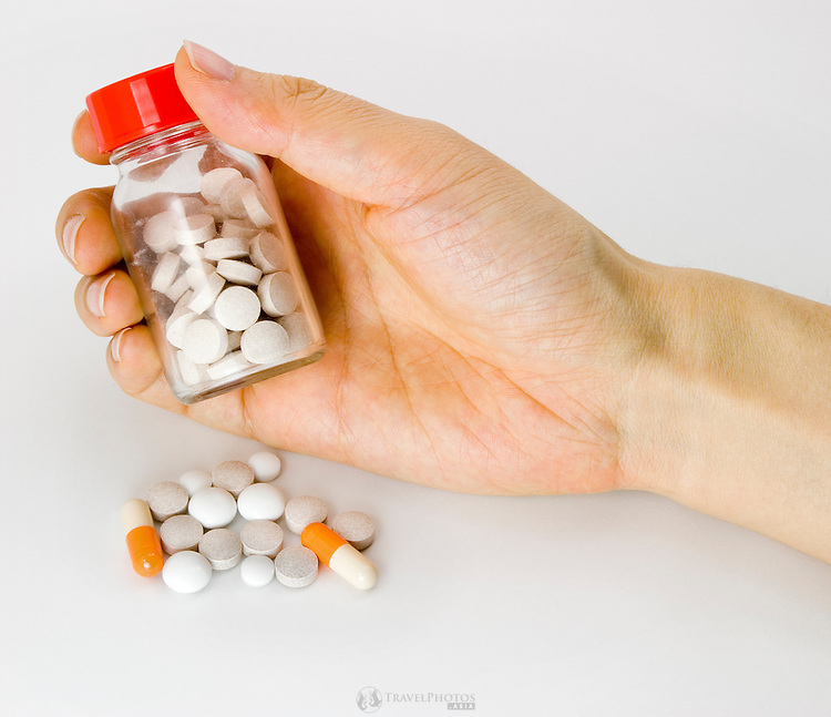 A woman's hand holding a bottle of assorted medicines and vitamin supplements.
