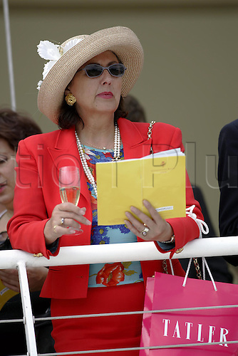 27 July 2004: A Lady consulting her race card at Goodwood Photo: Glyn Kirk/Action Plus...horse racing 040727 hat fashion race card glorious women champagne