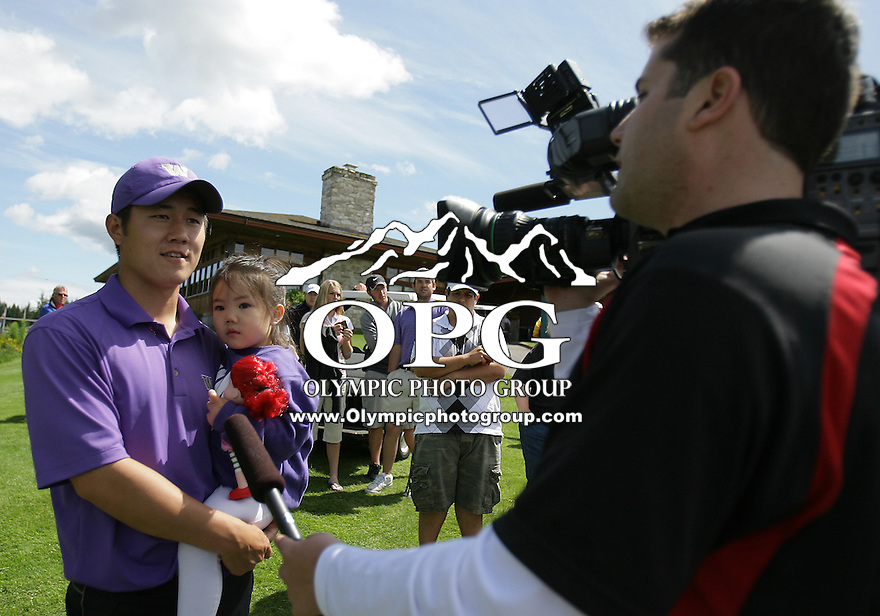 Washington's Richard Lee holding his daughter Israella gets interviewed by channel 4 news reporter Craig Newcom after winning the NCAA West Regionals at Gold Mountain Golf course in Bremerton, WA.
