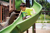 NWA Democrat-Gazette/CHARLIE KAIJO Royce Katt, 4, of Rogers reacts as he slides down a hot slide during a hot day, Monday, July 2, 2018 at Lake Atalanta Park in Rogers.