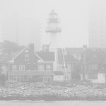 Sandy Hook Lighthouse on a foggy day. A selective color phoyo, the red light can be seen shining through the mist.