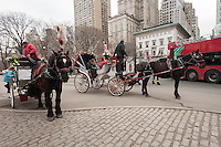 "Carriages and their horses are seen in the Central Park area in New York on Tuesday, December 31, 2013. Mayor-elect Bill De Blasio reiterated his position on dismantling the industry and working with the drivers to replace them with electric-powered ""antique"" automobiles. Animal rights groups have been lobbying for the end of carriage horses for years claiming that they are inhumane. (© Ricard B. Levine)"