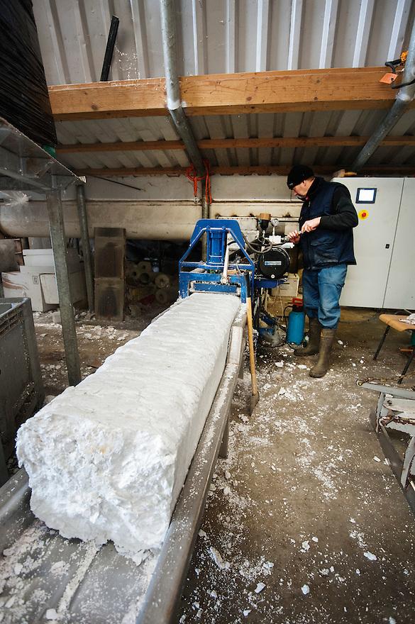 Nederland, Urk, 25 nov 2013<br /> Recyclingbedrijf de Vries, gespecialiseerd in tempex recycling.<br /> Samengeperst tempex komt uit machine. Hiervan kan weer nieuw tempex gemaakt worden.<br /> Foto: Michiel Wijnbergh