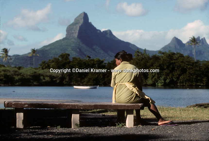 "A cleaning lady sits on a bench with the Montagne du Rempart, called the ""Matterhorn"" of Mauritius, in the background in 1996."