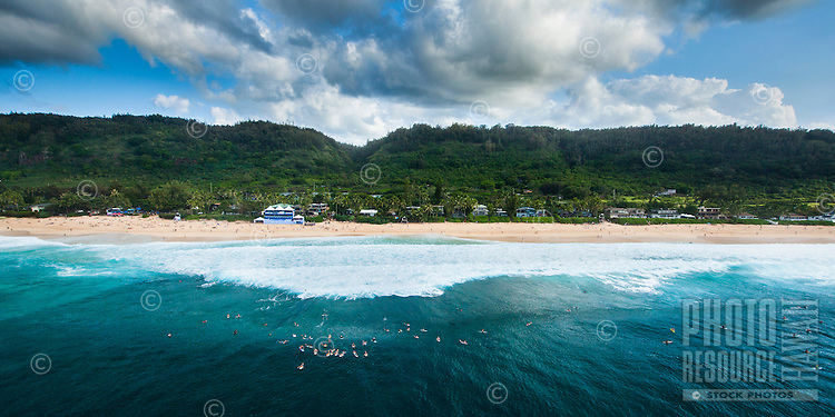 Surfers at Pipeline wait for a set to roll in; the Pipe Master tent can be see on the distant shore, North Shore, O'ahu.