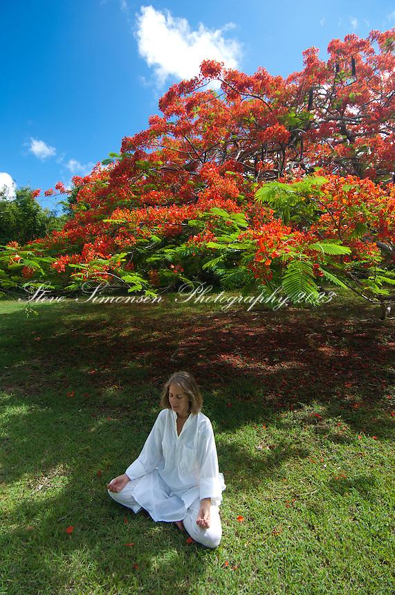 Woman meditating under a flamboyant tree at Caneel Bay Resort<br /> Virgin Islands National Park<br /> St. John, U.S. Virgin Islands